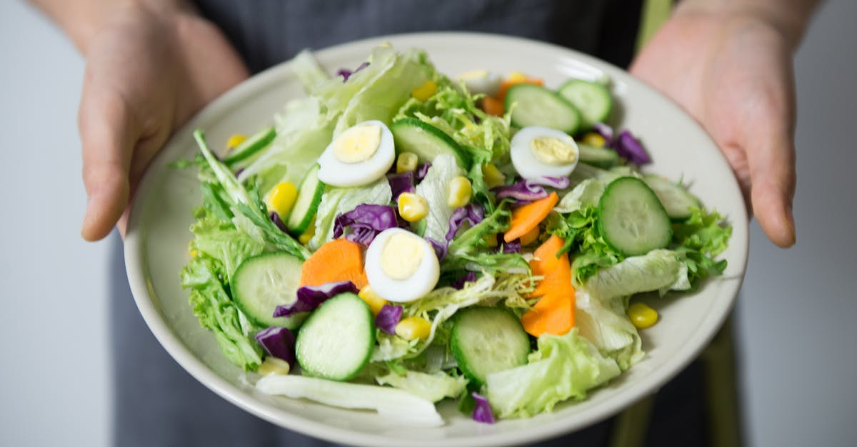 A person holding a bowl of salad